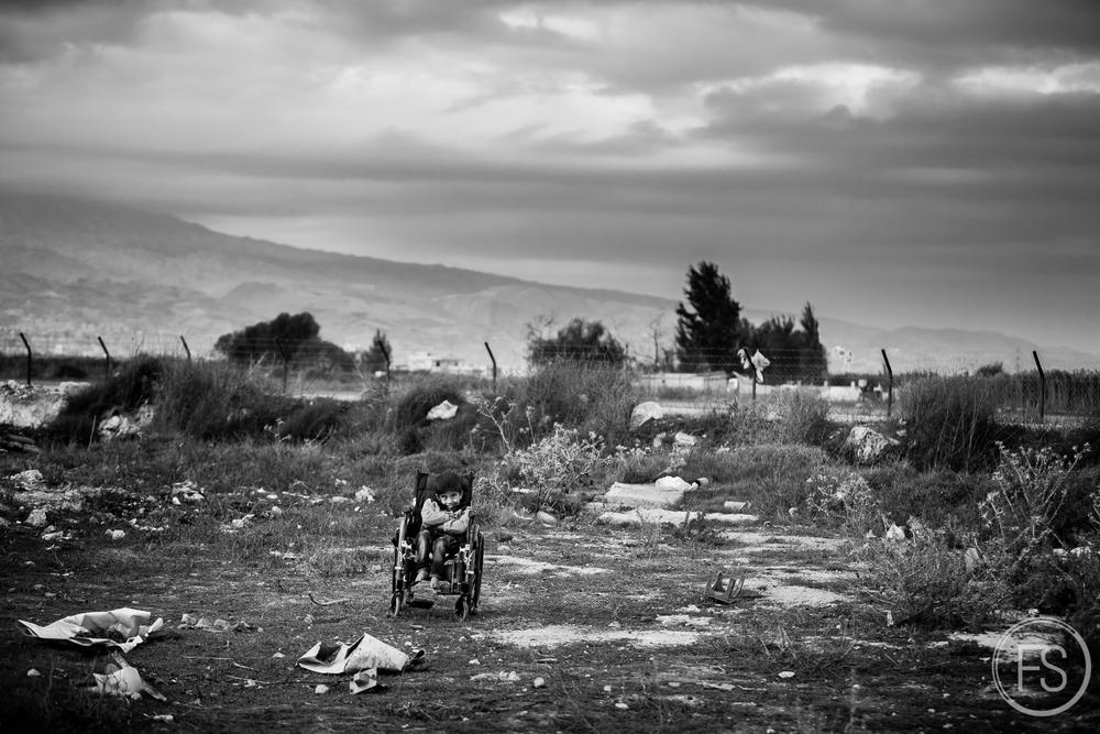 Un jeune garçon handicappé est placé à l'écart dans un champ avoisinant un camp de réfugiés dans la vallée de la Bekaa, Liban. Il sourit quand même.