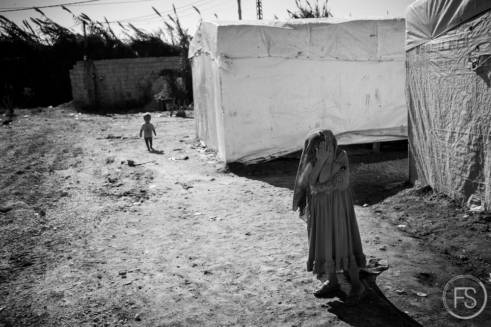 Une jeune fille couvre son visage. La grande majorité des réfugiés sont syriens et ont traversé la frontière avoisinante, à quelques kilomètres du camp. District d'Akkar, nord du Liban.