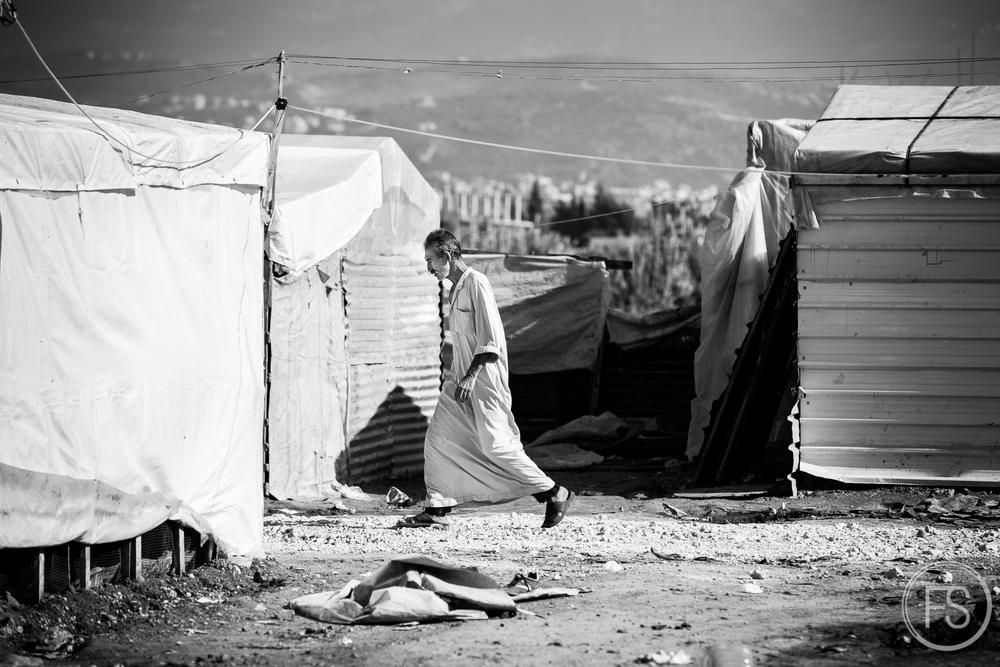 Un homme marche dans les allées d'un camp de réfugiés dans le district d'Akkar. La situation politique est extrêmement complexe pour eux puisque le gouvernement libanais ne les donne pas le statut de réfugiés et ne reconnait aucun camp sur son territoire. Cela fait en sorte qu'ils doivent payer un loyer pour occuper les terres en plus de diminuer la capacité des ONGs à intervenir.