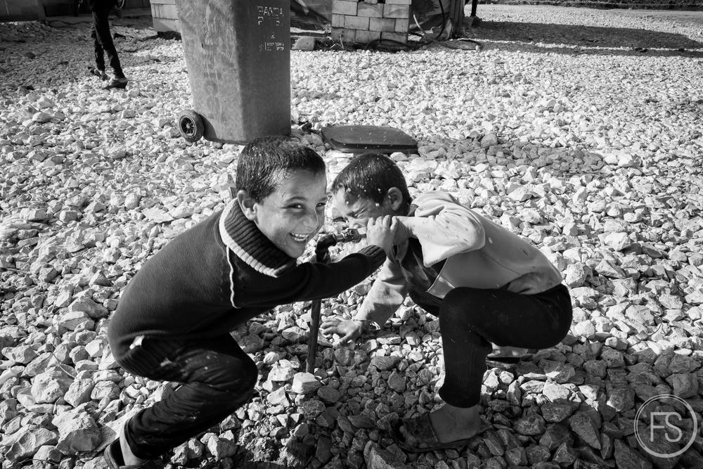 Des enfants jouent et se lavent avec robinet. Un approvisionnement régulier par des camions citernes leur apporte suffisamment d'eau mais celle-ci n'est pas toujours complètement sécuritaire et apte à la consommation. Vallée de la Bekaa, Liban.