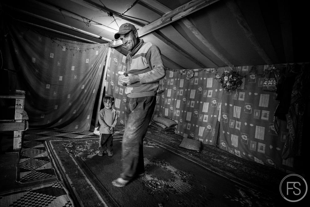 Un homme avec son fils à l'intérieur de la tente où ils demeurent. La plupart des tentes sont similaires et bâtis de façon précaire mais pour le long terme. Des poutres en bois, des tapis au sol et des toiles faisant office de murs et toits. L'électricité (et parfois la télévision!) y est souvent disponible mais constitue un risque important de courts circuits et de feu. Les hivers sont rudes dans la région et les tentes ne sont pas adaptées ni pour la neige qui s'accumule souvent et ni même pour la pluie qui peut pénétrer par le plancher. Vallée de la Bekaa, Liban.