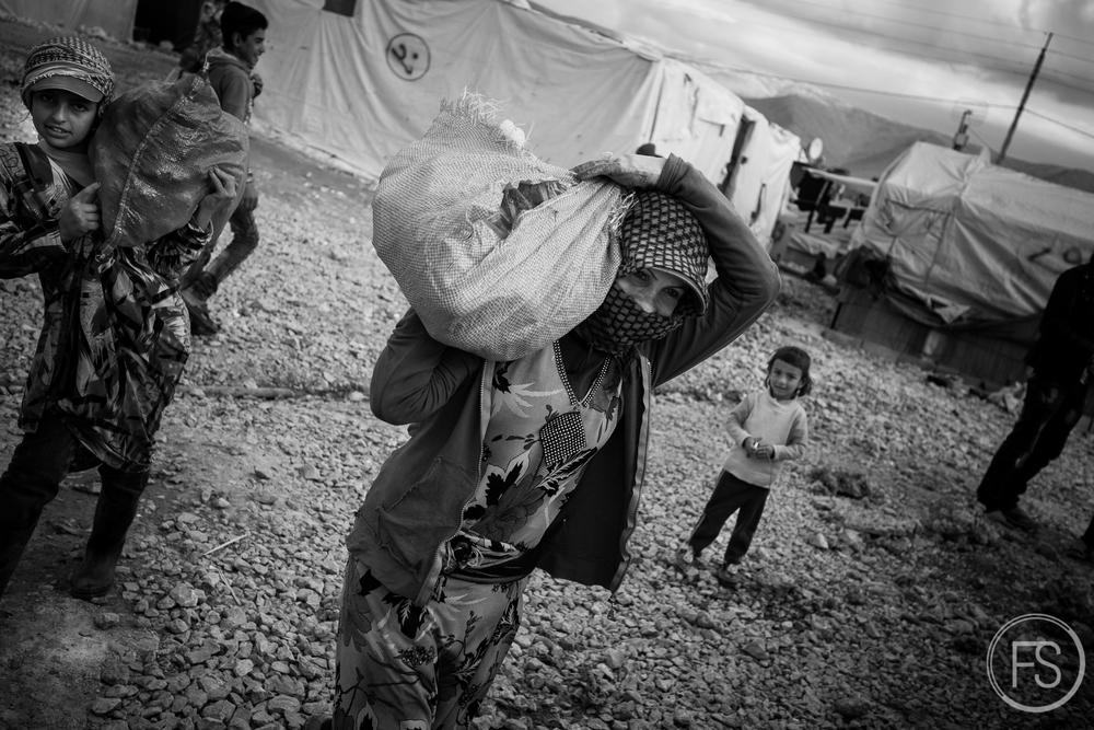 Une femme transporte un sac de nourriture sur son épaule dans un camp dans la vallée de la Bekaa, Liban. La nourriture provient de différentes sources; ONG, bénévoles, agriculture, magasin général, etc. Se nourrir est un enjeu quotidien dans les camps mais le manque de nourriture n'est pas le danger le plus pressant pour le moment.