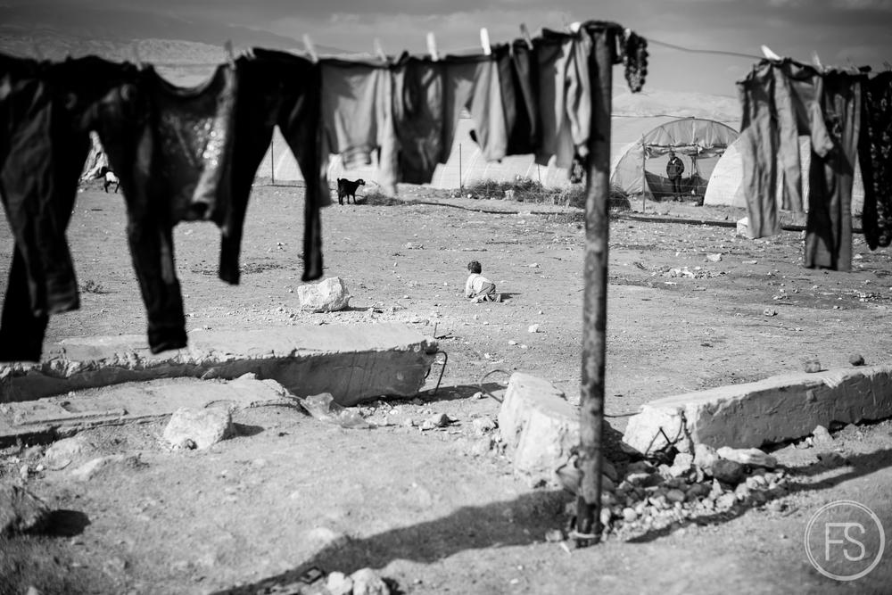 un bébé se promène dans un camp de la vallée de la Bekaa au Liban.