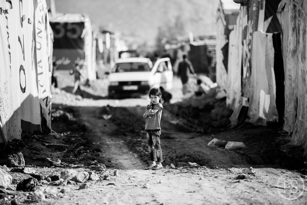 Une jeune fille attend dans une allée d'un camp de réfugiés de la vallée de la Bekaa, Liban.