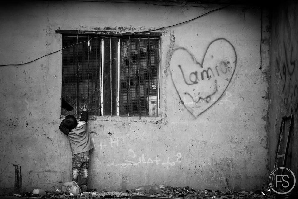 Un enfant tente de récupérer un objet à l'intérieur d'un abri dans un camp de la vallée de la Bekaa, Liban.