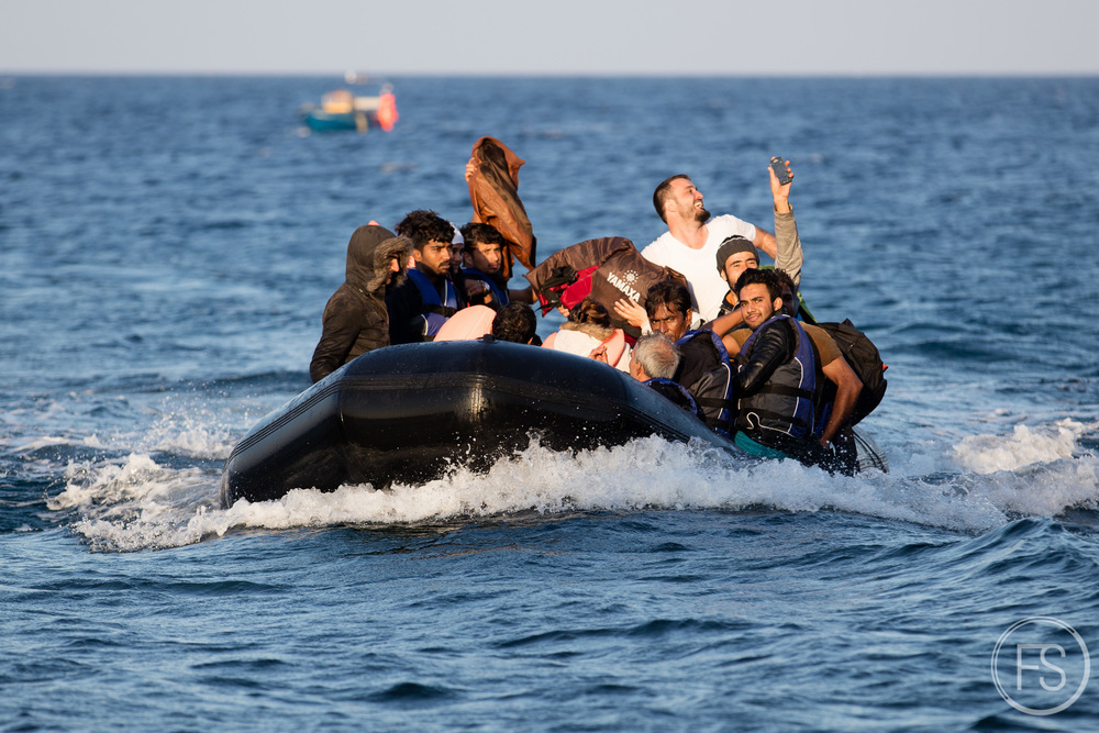 A boat full of refugees  arrives from the Turkish coast. A man smiles while taking a selfie before reaching the shore. When everything goes well, refugees are happy to arrive and celebrate accordingly. The journey usually takes two hours and the boats are handled by a refugee which will have  received very basic instructions on how to operate it and where to go. The smugglers do not care  about well-being of refugees and will often threaten them at gunpoint if refugees refuse to leave when weather conditions are too harsh. It's not unusual to see injured refugees arriving on the island after confrontations with smugglers.