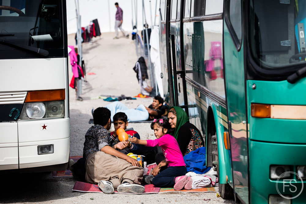 A family waits among the buses at the camp of Oxy near Molyvos. After landing on the shores, refugees are divided between the nearest camps and must wait for a bus to bring them to Mytilini where they can take the ferry to Athens. Big NGOs like UNHCR manage them which means they run on a very eclectic basis. There can be dozens of buses everyday as there can be days without a single one, making it really hard to manage for volunteers and a stressful situation for refugees who do not understand what is happening. On days where there are official visits on the island by high ranked officials such as Greek president or UNHCR high commissioner, buses usually stop completely to make some parts of the island look emptier and well managed, causing chaos elsewhere.