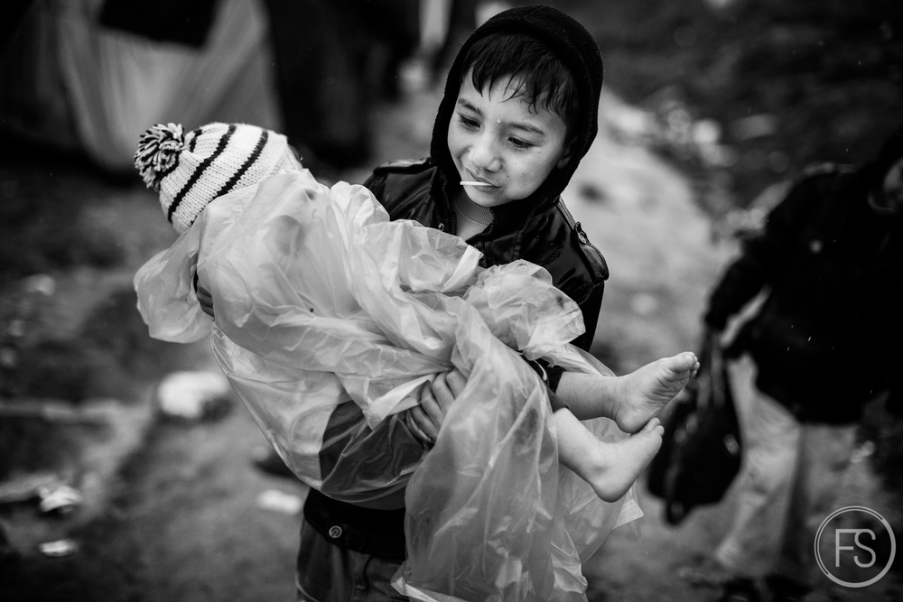 A young boy carries his little brother in the registration camp of Moria while the rain is falling.