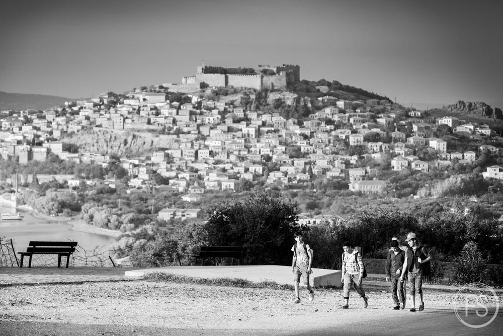 Un groupe de réfugiés marchent dans les collines sur l'ile de Lesvos avec la ville de Molyvos et son chateau en arrière-plan. Les paysages féériques de l'ile contrastent énormément avec les scènes difficiles s'y déroulant et constituent des situations surréelles.