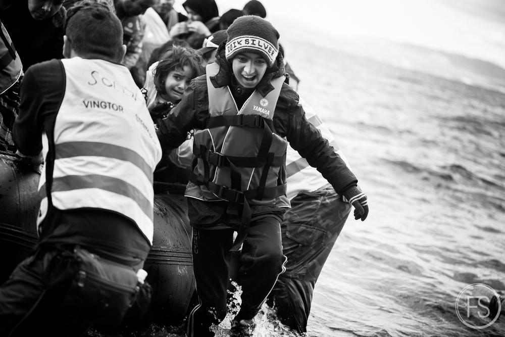 Un jeune réfugié débarque du bateau alors qu'un bénévole en aide d'autres sur la plage de Skala Sikamineas. La plupart des bateaux arrivant sont aidés par des équipes de bénévoles qui assistent les réfugiés. Ceux-ci sont habituellement trempés et ont besoin de vêtements secs rapidement. Sortir des bateaux est particulièrement ardu pour les plus âgés et les handicappés.