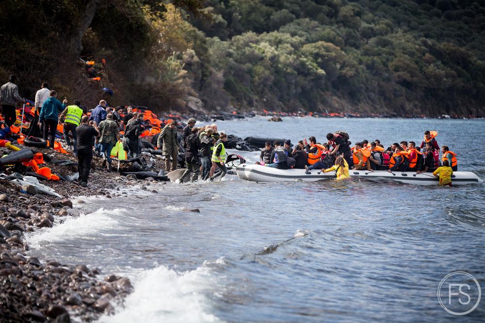 Des bénévoles et des journalistes se préparent à l'arrivée d'un bateau alors que des sauveteurs s'apprêtent à leur porter assistance. Il y a normalement suffisamment de personnes en support aux bateaux, parfois trop. Les nombreux journalistes sont souvent une nuisance aux bénévoles (eux aussi parfois trop nombreux) qui tentent d'amener tout le monde sur la terre ferme.