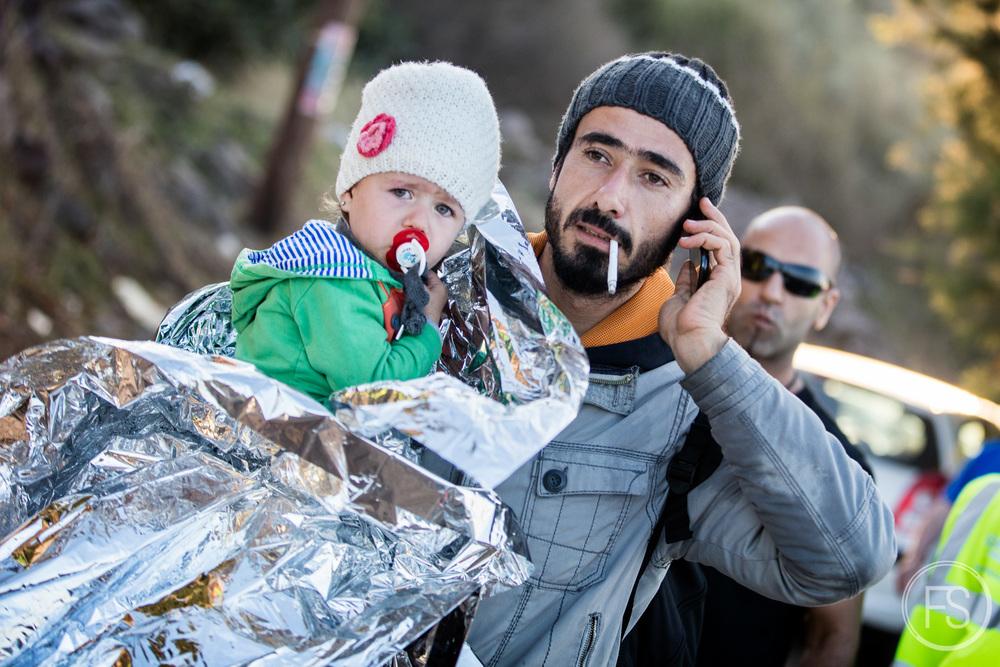 Un homme transporte sa fille dans une couverture d'urgence en parlant avec sa famille au téléphone. Après les réjouissances, le premier réflexe des réfugiés en arrivant sains et saufs est de contacter leurs proches afin de les rassurer. Il est courant de voir les réfugiés avec des téléphones intelligents. Ceux-ci sont incroyablement utiles puisqu'ils leur permettent non seulement de contacter leur famille mais également d'utiliser internet pour retrouver des proches, avoir des informations sur la route à emprunter ainsi que pour prendre des photos qui peuvent souvent être très utiles par la suite. Il est normal que les réfugiés aient les moyens de se payer une telle technologie, la plupart viennent de la classe moyenne et ne quittent pas leur pays pour des raisons économiques mais bien de sécurité.