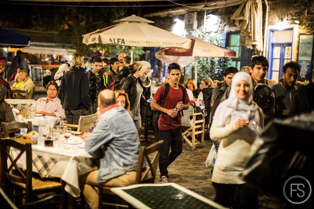 Un groupe de réfugiés venant tout juste d'arriver tard en soirée traversent le port de Molyvos où des touristes prennent leurs repas en terrasses. Même si la saison touristique est pratiquement terminée, des scènes de grands contrast peuvent se produire où d'un côté, des touristes profitent de leurs vacances et de l'autre, des réfugiés vivant une situation particulièrement éprouvante.