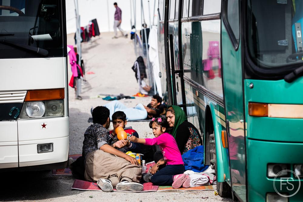 Une famille attend au milieu des autobus dans le camps de transit d'Oxy. Tout de suite après leur arrivée, les réfugiés sont envoyés vers le camp de transit le plus près. Des autobus les amènent ensuite dans les camps d'enregistrement près de Mytilène d'où ils prennent le bateau vers le port de Piraeus, Athènes. Il n'y a aucun horaire précis pour ces autobus qui sont gérés par les plus grosses ONG comme UNHCR ou MSF et ce manque de régularitécause énormément de confusion pour les réfugiés et bénévoles.