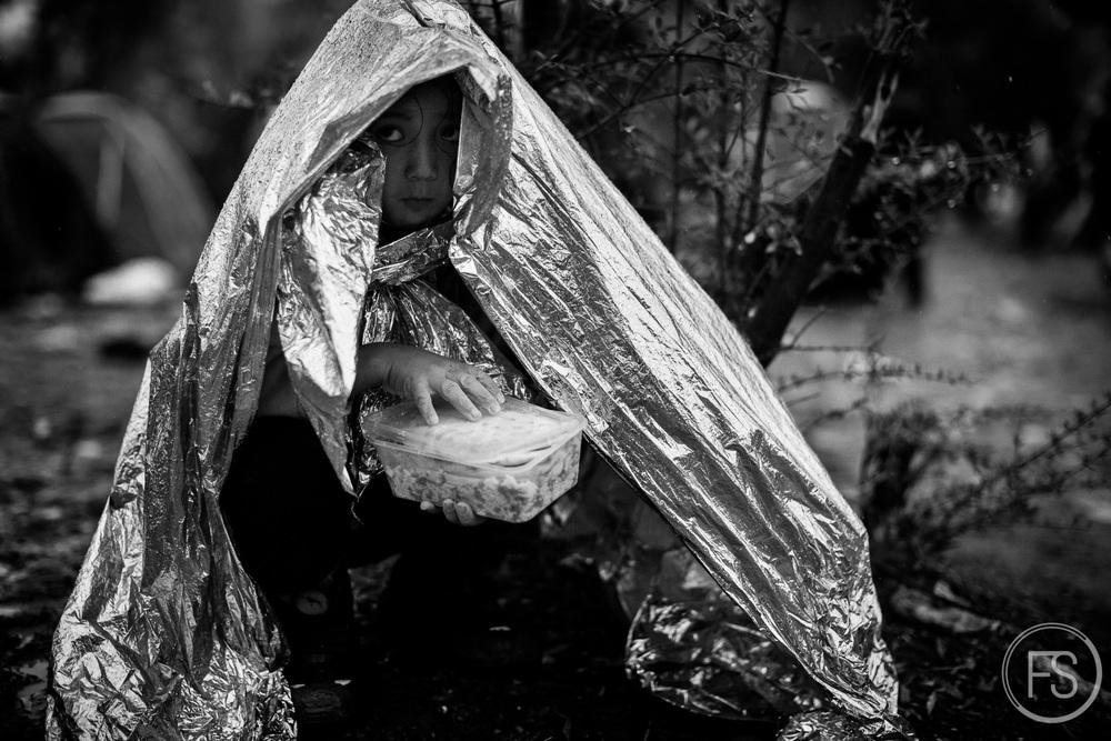 Une jeune fille tente de se protéger de la pluie sous une couverture d'urgence dans le camp d'enregistrement de Moria. Avant de pouvour poursuivre vers Athènes, chaque réfugié doit être enregistré. Ceux-ci doivent attendre leur tour à l'extérieur, sans le moindre abri ou aire d'attente organisée.Le processus peut prendre quelques heures ou quelques jours. Lorsqu'il pleut, comme dans ce cas-ci, les conditions sont misérables.