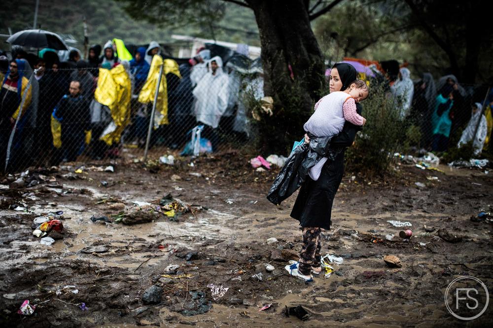 Une mère tient sa fille dans ses bras devant la file d'attente pour l'enregistrement dans le camp de Moria. Quitter la file revient à perdre sa place, ce qui peut parfois prendre plusieurs jours. Les conditions de vie ne sont pas adéquates à la dignité humaine.