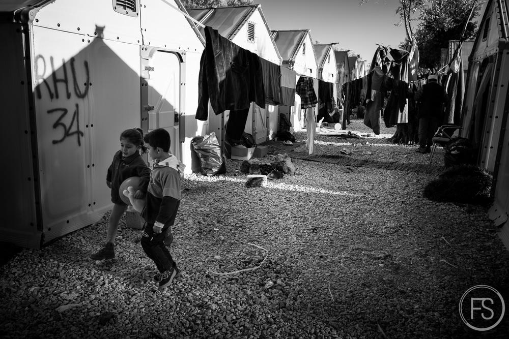 Deux enfants marchent entre les tentes du camps de Kara Tepe. Tout près de Moria, un camp où les conditions de vie sont incomparables. Du gravier, des abris solides contre la pluie, l'être humain est bien plus respecté.