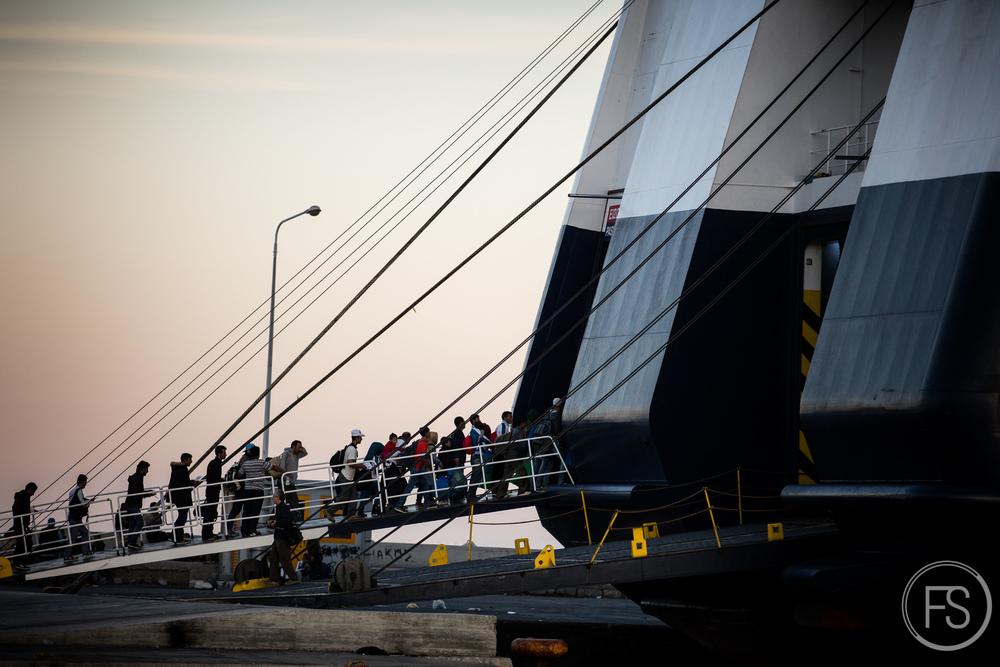 Des réfugiés embarquent dans le traversier qui les amènera au port de Piraeus à Athènes. Leur temp sur l'ile de Lesvos est maintenant derrière eux et un long périple commence afin de rejoindre leurs pays de destination finale.