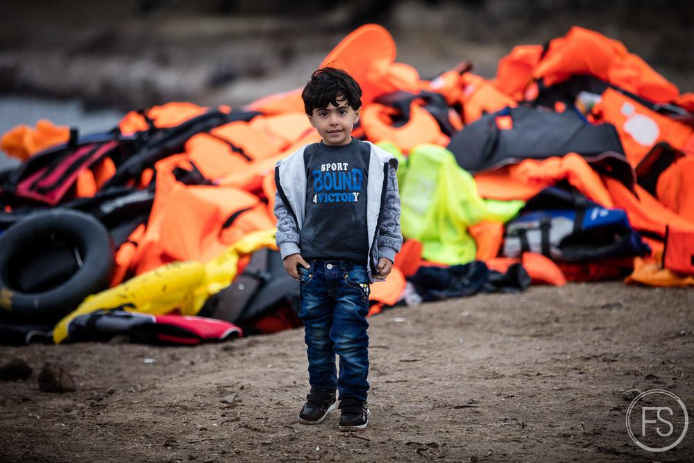 Un jeune garçon devant une montagne de gilets de sauvetage tout juste après avoir débarqué d'un bateau. Chaque bateau qui arrive représente une certaine quantité de déchets à gérer. Les réfugiés ne peuvent évidemment pas trainer avec eux les gilets trempés à la recherche d'une poubelle.