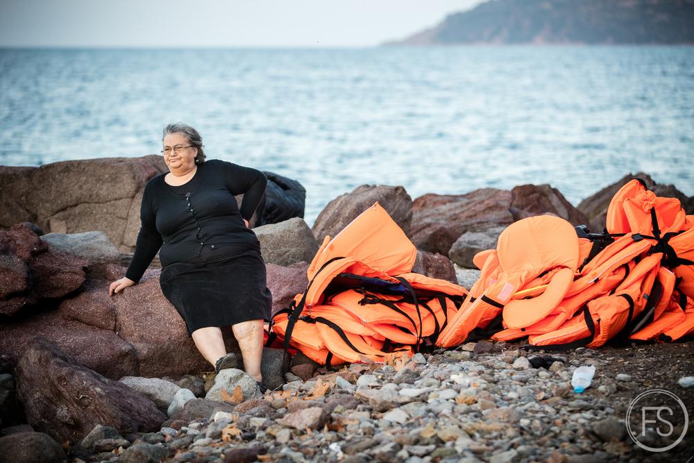 Une dame grecque résidant sur l'ile de Lesvos observe les arrivées de réfugiés sur le plages au milieu des gilets de sauvetage délaissés. Les conflits avec les résidants sont de plus en plus fréquents. Ceux-ci voient d'un mauvais oeil les répercussions environnementales des arrivées de réfugiés et s'inquiètent pour leur propre avenir.