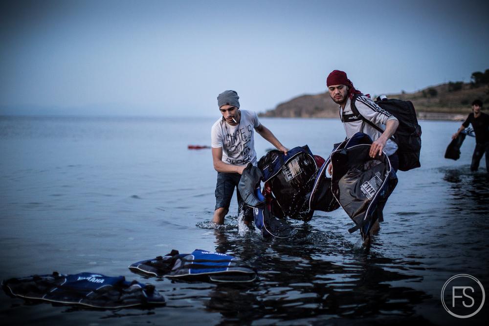 Deux réfugiés bravent les eaux glacées pour ramasser les gilets de sauvetage délaissés après leur arrivée. Il n'est pas rare de voir les réfugiés tenter de faire leur part mais il faut comprendre qu'avec tout le stress de la traversée et les émotions de l'arrivée, leur principale préoccupation n'est pas la propreté de l'ile.