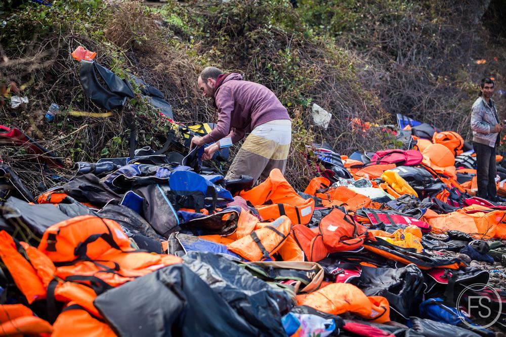 Un bénévole s'affaire à nettoyer les berges dans un amoncellement de gilets de sauvetage et de débris. Des organisations comme Volunteer's Coordination Lesvos organise des journées de nettoyage afin de protéger l'environnement de l'ile.