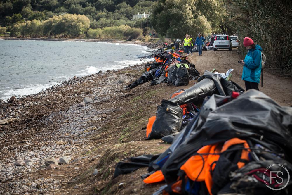 La plage de Skala Sikamineas nettoyée avec des piles de gilets prêts à être ramassés. Même lorsque les déchets sont regroupés, il est difficile d'organiser le ramassage et ensevelissage puisque la municipalité ne s'en charge pas elle-même. Le défi est continuel, dès le nettoyage terminé, tout est à refaire après quelques jours et quelques dizaines de nouvelles arrivées.