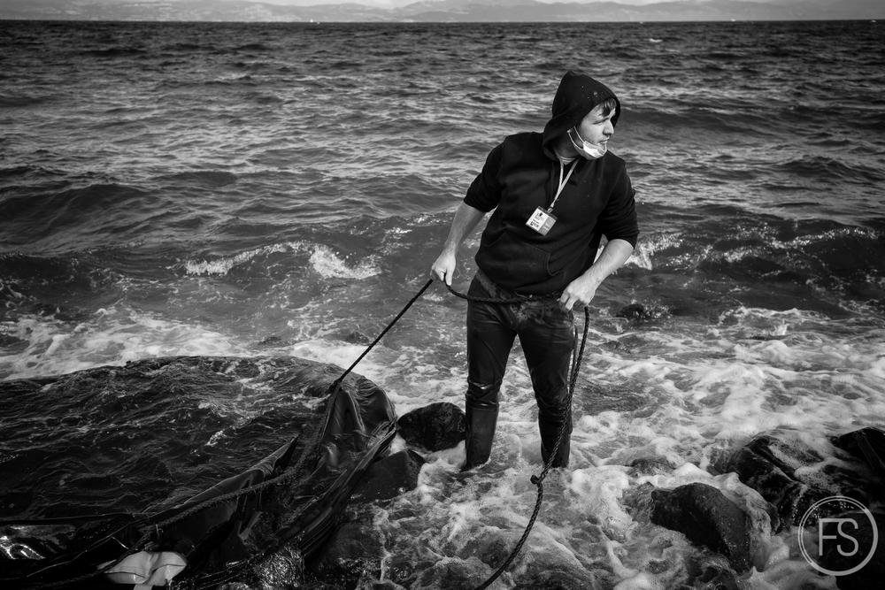 Antoine, un des organisateurs des journées de nettoyage peine à extirper les restes d'un bateau gonflable sur la plage. Il est important de continuellement nettoyer les plages et retirer les bateaux gonflables rapidement sinon ceux-ci sont graduellement recouverts de roches par la marée et deviennent de plus en plus difficiles à enlever.