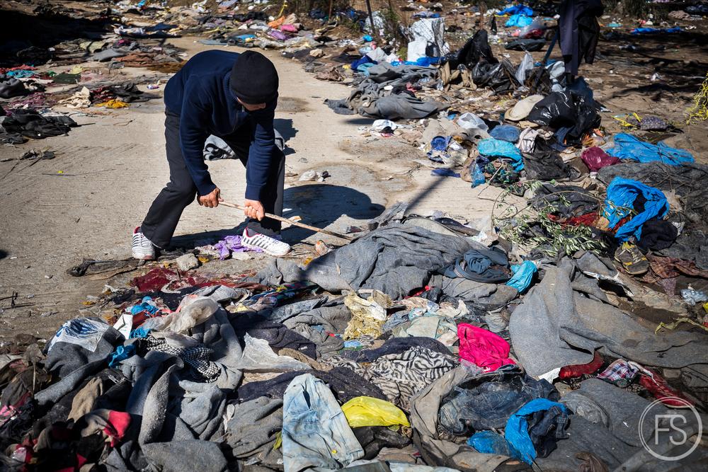 En attendant d'être admis à l'intérieur du camp d'enregistrement de Moria, un réfugié tente de nettoyer parmis les piles de déchets.
