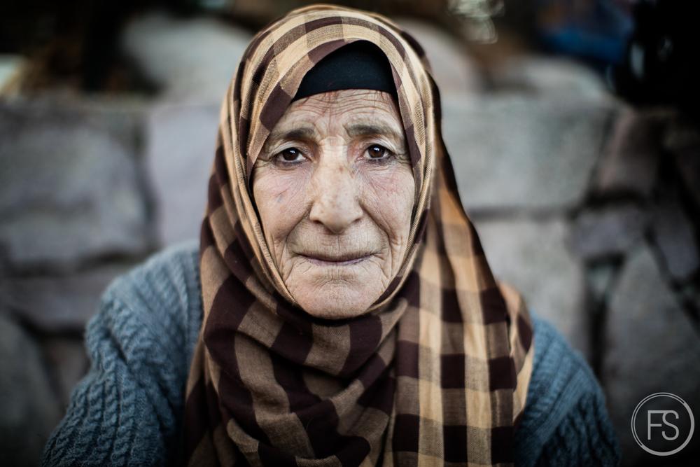 Une dame se remet de ses émotions après être arrivée par bateau pneumatique à la plage de Skala Sikamineas sur l'ile de Lesvos, Grèce.