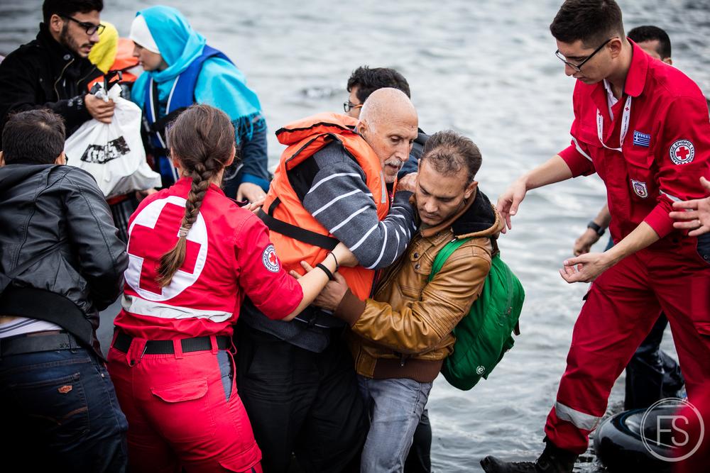 Un homme peine à sortir du bateau pneumatique duquel il est arrivé de la Turquie. Des équipes de bénévoles sont présentes pour faciliter l'arrivée sur la plage. Les enfants et les personnes âgées ont particulièrement de la difficulté à en sortir. Le danger est bien réel. Dans le chaos, il arive que des réfugiés perdent la vie en se noyant, si près du but. Lesvos, Grèce.