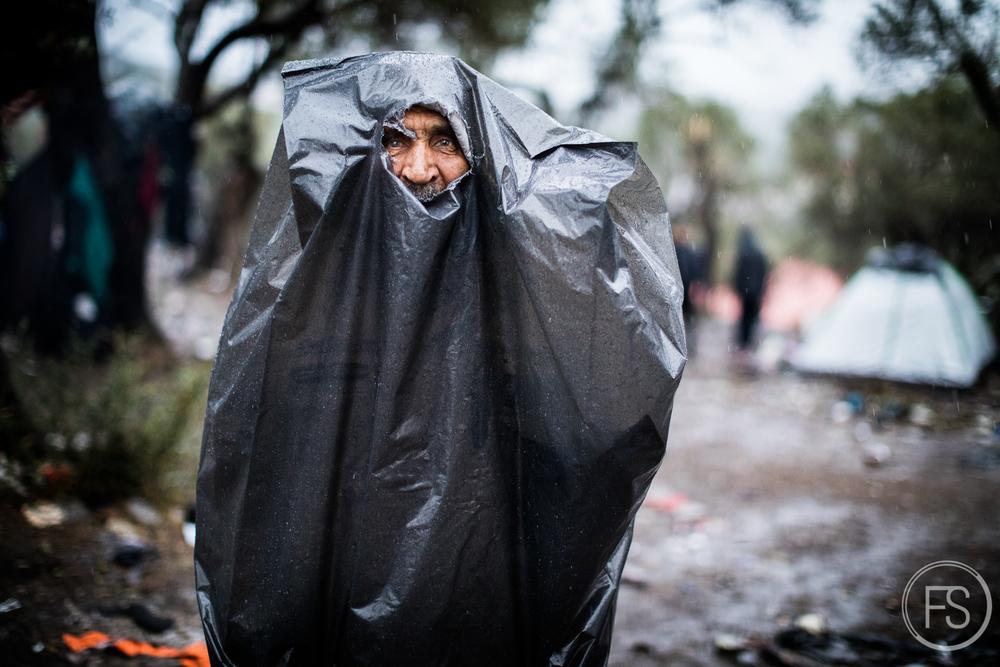 Un homme tente de se protéger de la pluie en enfilant un sac de poubelle dans le camp d'enregistrement de Moria sur l'ile de Lesvos. Les conditions de vie sont souvent ardues lorsque la pluie se met de la partie pour plusieurs jours et qu'aucun refuge n'est disponible. Lesvos, Grèce.