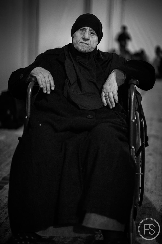 Une femme âgée en fauteuil roulant attend dans une tente du camp de transit d'Idomeni à la frontière entre la Grèce et la Macédoine. Un fauteuil roulant aussi lourd représente un fardeau important pour sa fille qui ne peut transporter sa mère toute seule. Idomeni, Grèce.