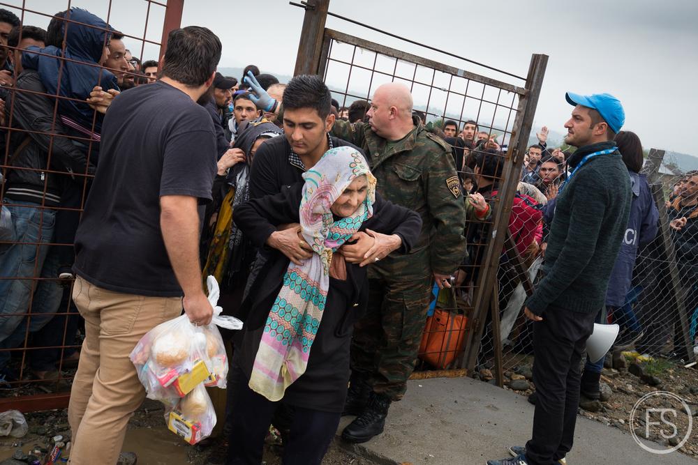 Une femme se fait aider pour passer les clôtures du camp de Gevgelija au milieu du chaos. Macédoine.