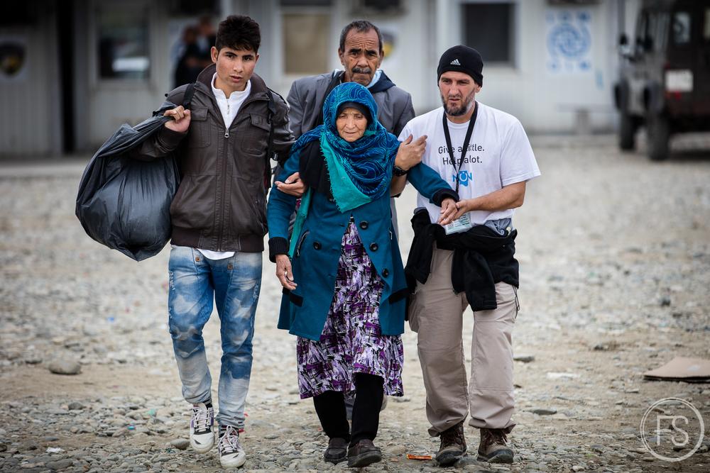 Une femme est aidée par un membre de sa famille et un volontaire pour se rendre au train à l'intérieur du camp de Gevgelija. Les bénévoles des différentes organisations jouent un rôle primordial pour aider les réfugiés plus vulnérables. Gevgelija, Macédoine.