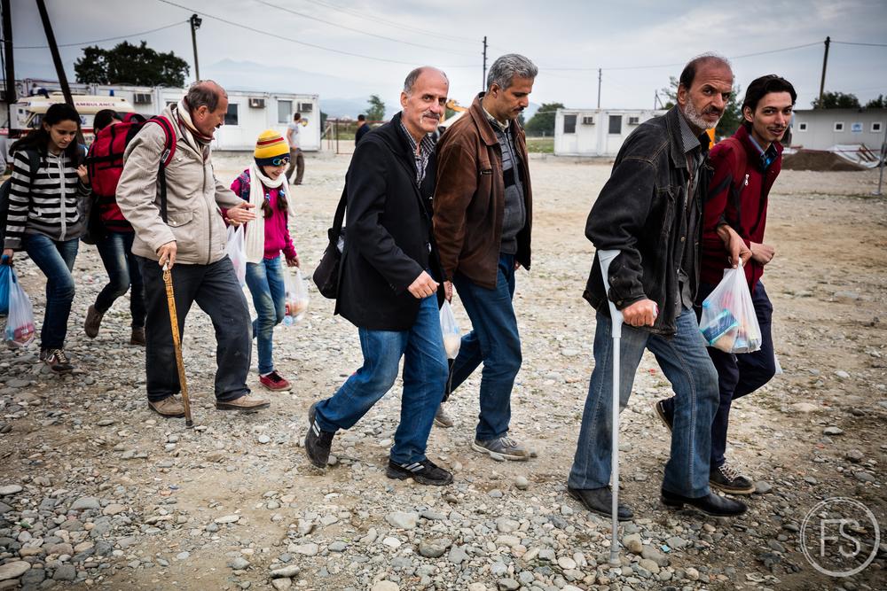 Un groupe traverse le camp de Gevgelija. De longues heures de marches avec cannes et béquilles n'ont pas estompé le sourires de ces hommes. Gevgelija, Macédoine.