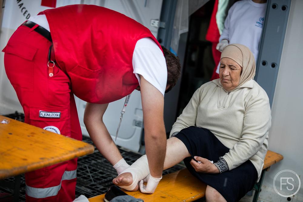 Une femme se fait mettre un bandage au pied par un médecin de la Croix Rouge Macédonienne. Marcher de longues distances et rester debout sans endroit convenable pour se reposer est particulièrement difficile et dommageable pour les personnes âgées qui sont plus vulnérables. Gevgelija, Macédoine.