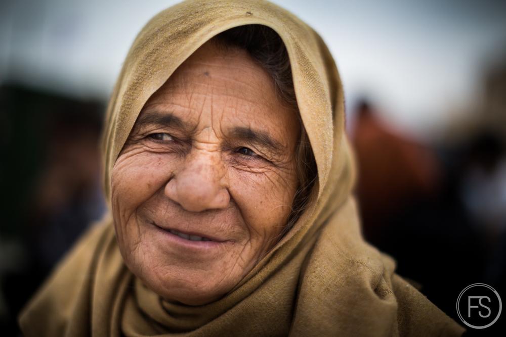 Une dame âgée garde le sourire malgré les difficultés du périple. Gevgelija, Macédoine.