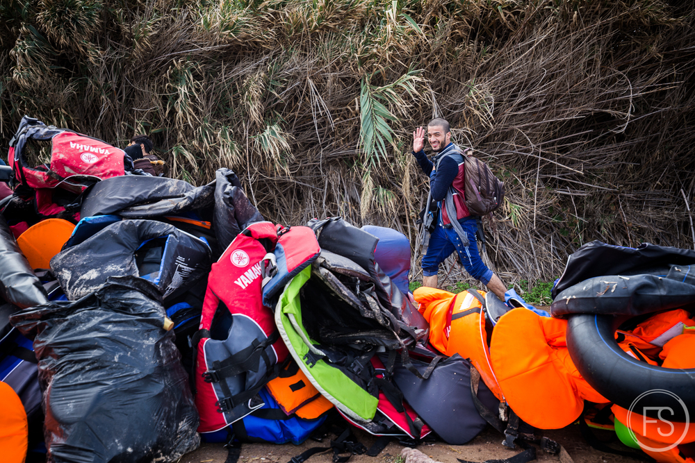 A man smiles and waves at the camera while walking in front of a mountain of life jackets. The municipality has not yet organized any kind of trash collection on the shores.