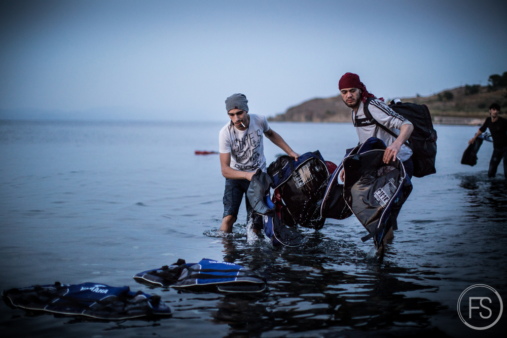 Two refugees who just arrived are cleaning up the shores of the life jackets discarded by other people on their boats. It is not unusual to see refugees helping to clean up but it is understandable that with all the stress and emotions from the crossing, cleaning is not their priority.