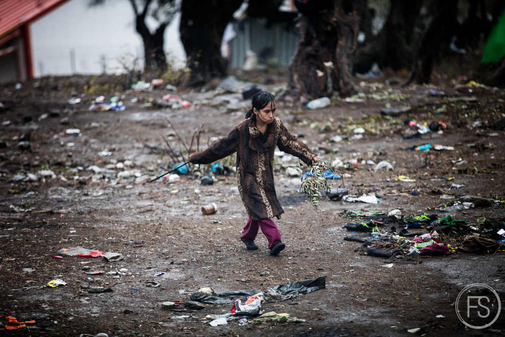 A little girl walks under the rain among the trash in the registration camp of Moria on Lesvos. Rain can last for a few days and pose a serious health threat when trash soaks in puddles of water for days.