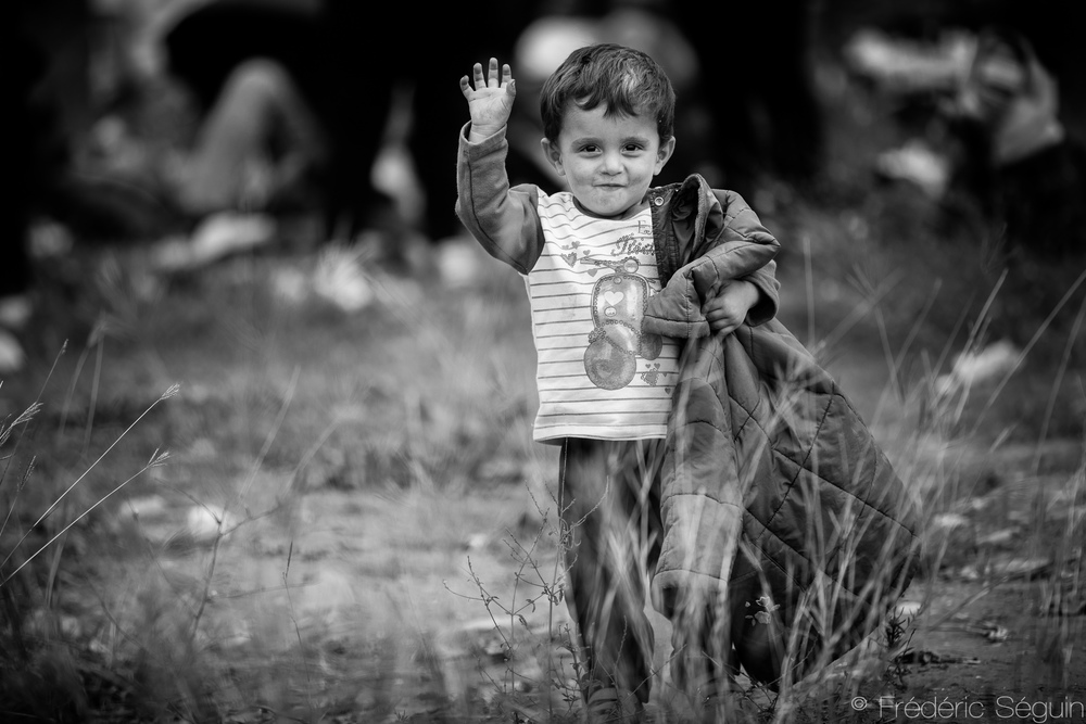 Brave little man walking with his family from the Greek border of Idomeni to Macedonia (FYROM) takes time to wave and smile at the lucky photographer.  To this day, I can't help but smile just by looking at the picture. Since it was taken, Macedonia (FYROM) closed its borders to all refugees except Syrians, Afghans and Iraqis. Gevgelija, Macedonia (FYROM).