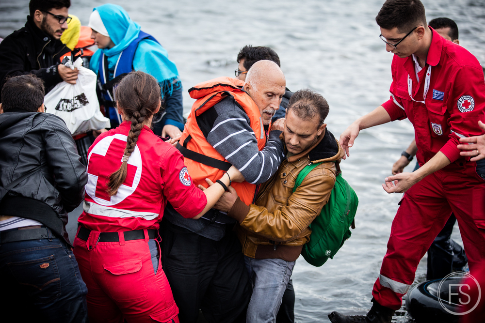 A man struggles to get out of the dinghy boat arriving on the shore. All the volunteers are doing an incredible job saving lives but in the chaos, tragedies happen and many lose their lives so close to their goal. Lesvos, Greece.