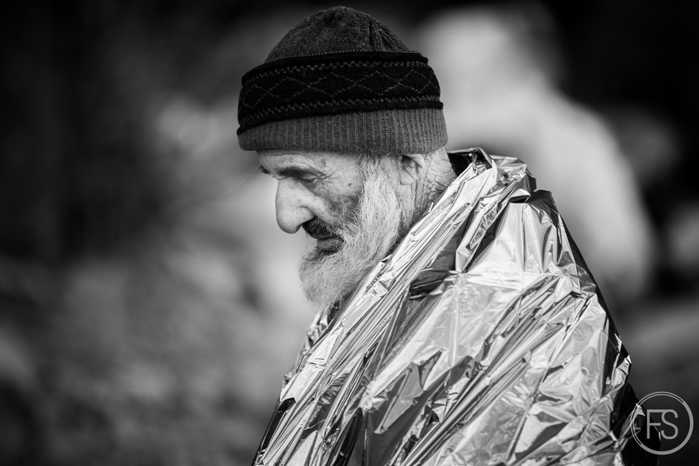 Having just arrived on the island, this man has the most dangerous part of the journey behind him but still many days of walking ahead. The thermal blanket will keep him warm for a while but he will need dry clothes as soon as possible. Lesvos, Greece.