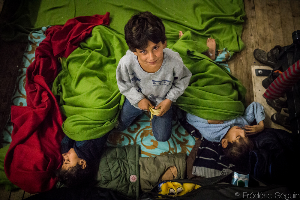 Taking care of his two sleeping brothers, this brave refugee boy waits for their turn to get registered in the camp of LaGeSo, Berlin, Germany.