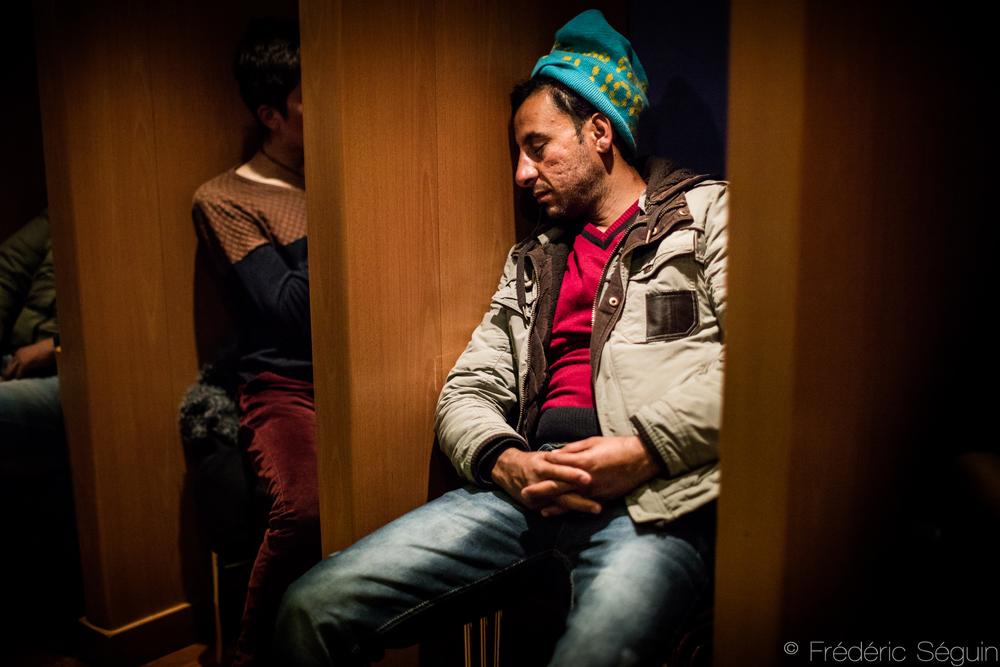Un homme parvient à dormir dans le traversier entre l'ile de Lesvos et le port de Piraeus. Les occasions de se reposer se feront rares au long du périple. Mer Égée, Grèce.