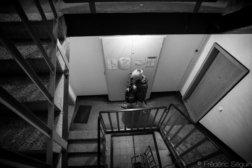 A man walks down the stairs of an apartment building partially reserved for refugees.Long term accommodation is assigned when there is enough availability.Eberswalde, Germany.