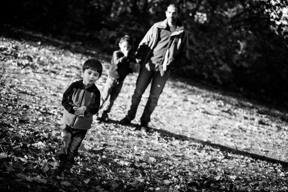 A family takes a walk in the park, enjoying the autumn leaves, as far away from the bombs as possible.Eberswalde, Germany.