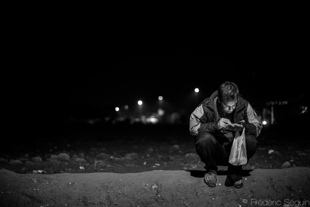 Au milieu de la nuit, un homme communique avec sa famille en attendant de pouvoir traverser la frontière. Les téléphones intelligents sont extrêmement utiles aux réfugiés afin de garder contact avec leur famille. Eidomeni, Grèce.