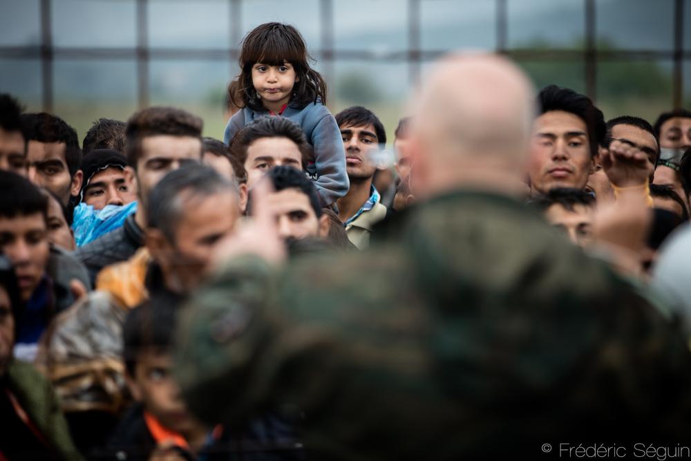 Sur les épaules de son père, une petite fille observe, découragée, la bousculade pour entrer à l'intérieur du camp de transit. Ces scènes sont rares mais surviennent quand même à l'occasion. Gevgelija, Macédoine (ARYM)